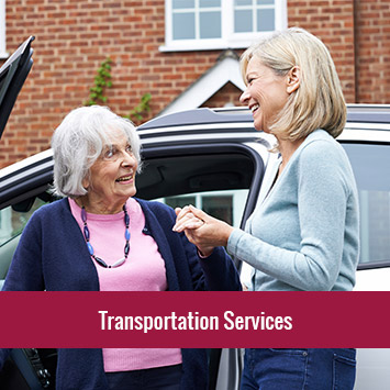 Middle-aged woman helping an elderly women out of a vehicle | Transportation Services